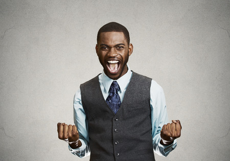 excited: Closeup portrait happy successful student, business man winning, fists pumped celebrating success isolated grey wall background. Positive human emotion, facial expression. Life perception, achievement