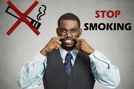 Portrait young man, pinches his nose, something stinks bad smoke smell, grey wall background, stop smoking sign. Negative face expression, body language, reaction Smoking restricted area. Breath smell photo