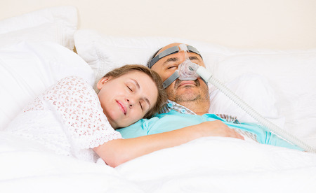 sleeping face: Man with sleeping apnea and CPAP machine, devise, asleep peacefully with wife in bedroom their house. Healthcare management patient with sleep apnea. Human respiratory, airway, system health issues.