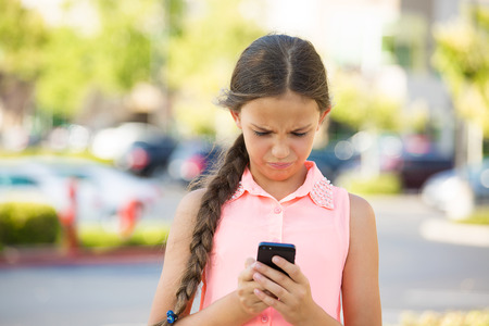 Important text message. Portrait teenage girl looking concerned with text message on her phone, isolated outdoor street background. Human face expressions, emotions, body language, reaction, feelings photo