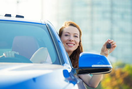 Closeup portrait happy, smiling, young attractive woman, buyer sitting in her new blue car showing keys