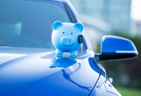 car dealer: Closeup of piggy bank and key on car hood Stock Photo