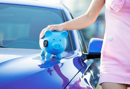 Vrouw met een spaarpot, sleutel op de auto motorkap Stockfoto - 31097579