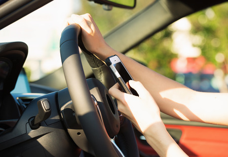 Closeup of businesswoman hands, sending text message on smart phone while driving
