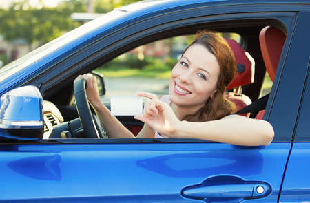 Young woman in new car showing blank drivers license or sign out, through side car window photo