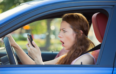 Closeup portrait of young shocked woman driver, driving in car checking smart phone annoyed by bad text message photo