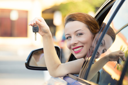 Closeup of happy, smiling, young attractive woman, buyer sitting in her new blue car showing keys photo