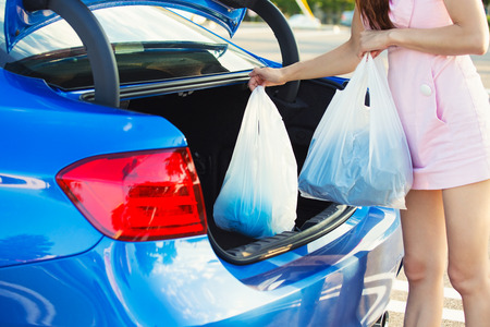 errands: woman putting shopping bags inside trunk of her blue car Stock Photo