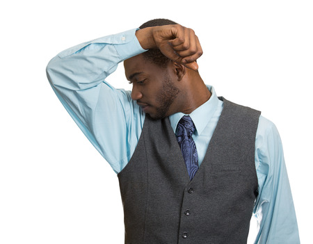 intolerable: Closeup of young man, smelling sniffing his armpit, isolated on white background