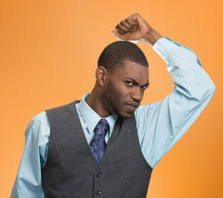 Closeup of young man, smelling sniffing his armpit, isolated on orange background
