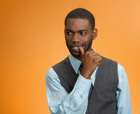 black business men: Closeup portrait of man with finger in mouth isolated on orange background