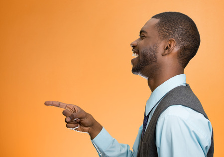 fullness: Closeup side view portrait of happy young man, laughing, pointing with finger isolated on orange background