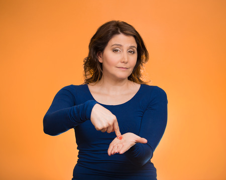 Upset woman gesturing pay me my money back, finger on palm gesture, isolated orange background. Human face expressions, emotion feelings body language, non verbal communication. Financial debt concept Stock Photo