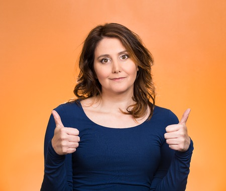Closeup portrait, young, middle aged woman, mother being excited, giving thumbs up, isolated orange background. Positive human emotions, facial expressions, feeling, signs, symbol, attitude, reaction photo