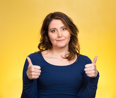 Closeup portrait, young, middle aged woman, mother being excited, giving thumbs up, isolated yellow background. Positive human emotions, facial expressions, feeling, signs, symbol, attitude, reaction photo