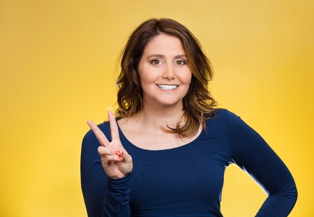 Closeup portrait, young, middle aged smiling woman, giving peace, victory, two sign, with hands isolated yellow background. Positive emotions, face expressions, feeling, attitude, reaction, perception