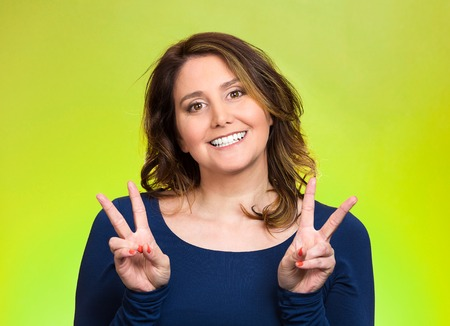 Closeup portrait, young, middle aged smiling woman, giving peace, victory, two sign, with hands isolated green background. Positive emotions, face expressions, feeling, attitude, reaction, perception Stock Photo
