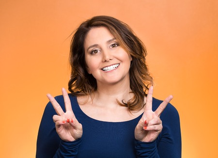 Closeup portrait, young, middle aged smiling woman, giving peace, victory, two sign, with hands isolated orange background. Positive emotions, face expressions, feeling, attitude, reaction, perception