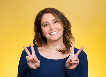 non verbal: Closeup portrait, young, middle aged smiling woman, giving peace, victory, two sign, with hands isolated yellow background. Positive emotions, face expressions, feeling, attitude, reaction, perception