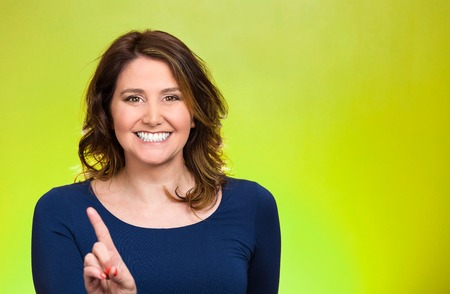 good deal: Closeup portrait young, middle aged smiling woman pointing at you camera gesture, pushing button, isolated green background. Positive human emotions, facial expression, feeling, signs symbol, reaction