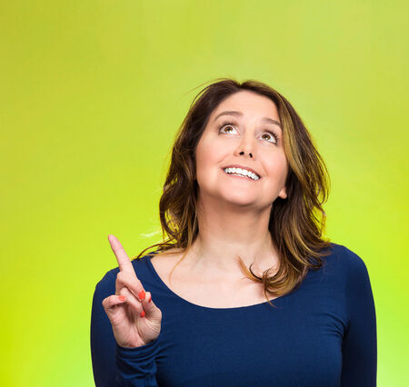 Closeup portrait surprised young happy, funny woman, just came up with idea aha, index finger pointing, looking up isolated green . Positive human emotion, facial expression, feeling, sign photo
