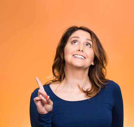 Closeup portrait surprised young happy, funny woman, just came up with idea aha, index finger pointing, looking up isolated orange . Positive human emotion, facial expression, feeling, sign photo