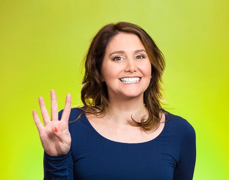 non verbal: Closeup portrait, young, happy, smiling woman, making four, 4 times sign gesture with hand fingers, isolated green . Positive human emotions, facial expression, feelings, attitude, symbols