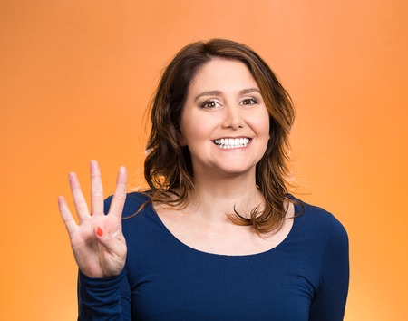 quadruple: Closeup portrait, young, happy, smiling woman, making four, 4 times sign gesture with hand fingers, isolated orange background. Positive human emotions, facial expression, feelings, attitude, symbols Stock Photo