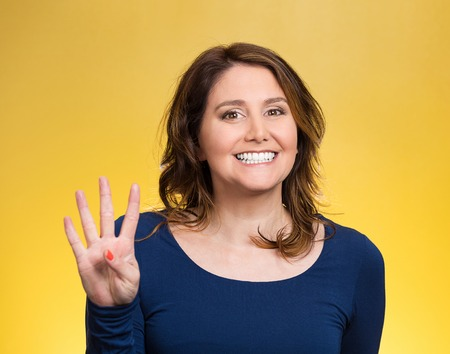 Closeup portrait, young, happy, smiling woman, making four, 4 times sign gesture with hand fingers, isolated yellow background. Positive human emotions, facial expression, feelings, attitude, symbols