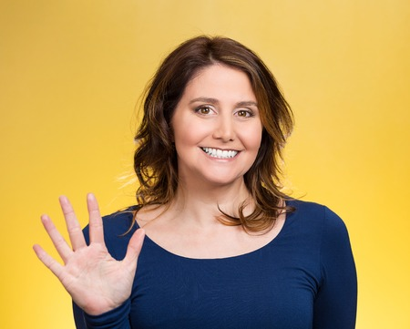 Closeup portrait, happy, smiling young woman making five times sign gesture with hand fingers, isolated yellow background. Positive human emotion facial expression feelings, attitude, symbol, reaction