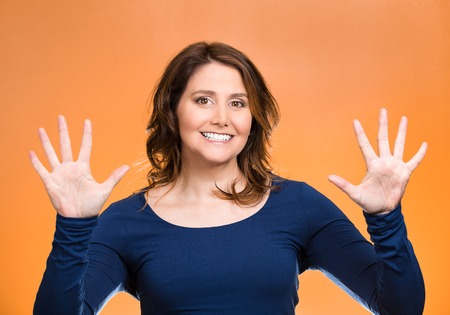 five people: Portrait, happy, smiling young woman making two times five sign gesture with hands, fingers, number ten isolated orange background. Positive human emotion facial expression feeling attitude, symbol, reaction Stock Photo