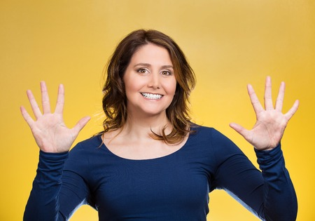 Portrait, happy, smiling young woman making two times five sign gesture with hands, fingers, number ten isolated yellow background. Positive human emotion facial expression feeling attitude, symbol, reaction photo