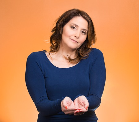 non verbal: Portrait young, middle aged smiling, happy, kind woman with raised up palms arms at you offering something, isolated orange background. Positive emotion facial expression sign symbol