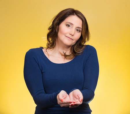 non verbal communication: Portrait young, middle aged smiling, happy, kind woman with raised up palms arms at you offering something, isolated yellow background. Positive emotion facial expression sign symbol