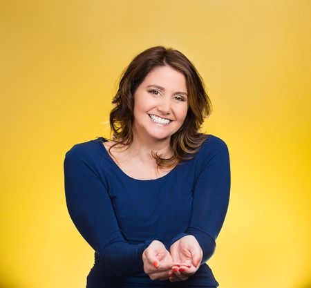 Portrait young, middle aged smiling, happy, kind woman with raised up palms arms at you offering something, isolated yellow background. Positive emotion facial expression sign symbol