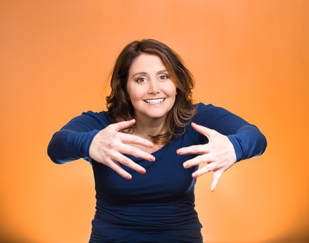 beckon: Closeup portrait young beautiful, middle aged smiling, happy, kind woman with raised up palms arms at you offering hug, isolated orange background. Positive emotion facial expression sign symbol