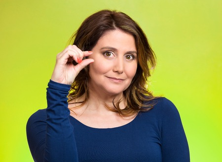 degrading: Closeup portrait, young middle aged woman, showing small amount gesture with hands, isolated green background. Human emotion facial expression feeling, body language, sign, symbol, reaction, perception