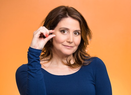 degrading: Closeup portrait, young middle aged woman, showing small amount gesture with hands, isolated orange background. Human emotion facial expression feeling, body language, sign, symbol, reaction, perception Stock Photo