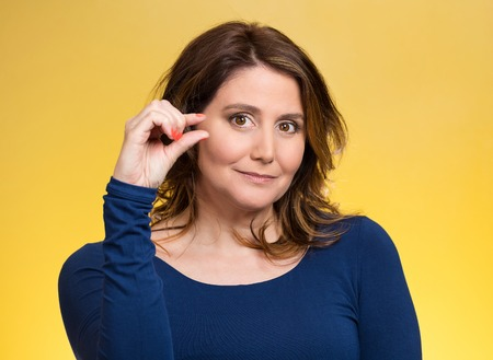 gestures: Closeup portrait, young middle aged woman, showing small amount gesture with hands, isolated yellow background. Human emotion facial expression feeling, body language, sign, symbol, reaction, perception