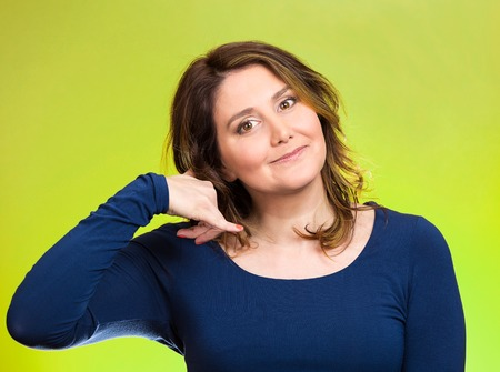 approachable: Closeup portrait headshot young single woman making call me gesture, excited happy student, worker, showing sign with hand shaped like phone isolated green background. Positive human emotion face expression
