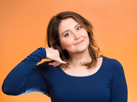 non verbal: Closeup portrait headshot young single woman making call me gesture, excited happy student, worker, showing sign with hand shaped like phone isolated orange background. Positive human emotion face expression Stock Photo