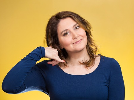 non verbal communication: Closeup portrait headshot young single woman making call me gesture, excited happy student, worker, showing sign with hand shaped like phone isolated yellow background. Positive human emotion face expression Stock Photo