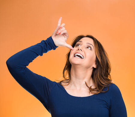 hammered: Portrait young, silly, goofy woman, gesturing with hand thumb to go party, get drunk, hammered, wasted, isolated orange background. Positive emotions, facial expressions, feeling, sign, symbol
