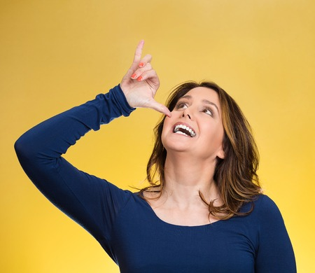 wasted: Portrait young, silly, goofy woman, gesturing with hand thumb to go party, get drunk, hammered, wasted, isolated yellow background. Positive emotions, facial expressions, feeling, sign, symbol