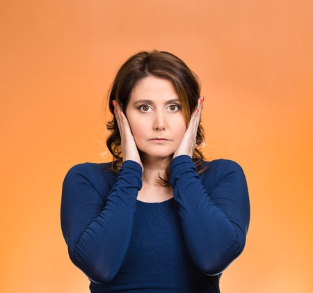 Closeup portrait attractive, peaceful, relaxed looking young woman, covering ears, eyes opened, isolated orange background. Hear no evil concept. Human emotions, facial expression, attitude photo