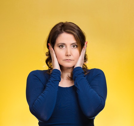 eyes opened: Closeup portrait attractive, peaceful, relaxed looking young woman, covering ears, eyes opened, isolated yellow background. Hear no evil concept. Human emotions, facial expression, attitude Stock Photo