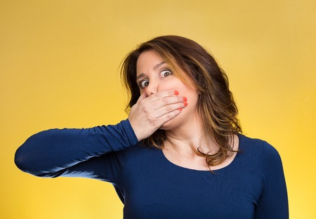 Closeup portrait middle aged business woman, worker, scared employee, covering mouth. Speak no evil concept, isolated yellow background. Human emotions, face expression, feeling, sign, body language