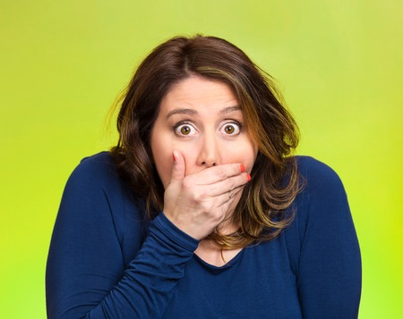 agitated: Closeup portrait middle aged shocked young woman, covering her mouth, wide open eyes, isolated green background. Negative human emotion, facial expression, feeling, signs, symbol, reaction Stock Photo