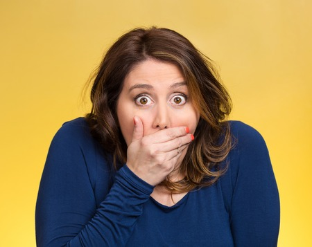 Closeup portrait middle aged shocked young woman, covering her mouth, wide open eyes, isolated yellow background. Negative human emotion, facial expression, feeling, signs, symbol, reaction Stock Photo
