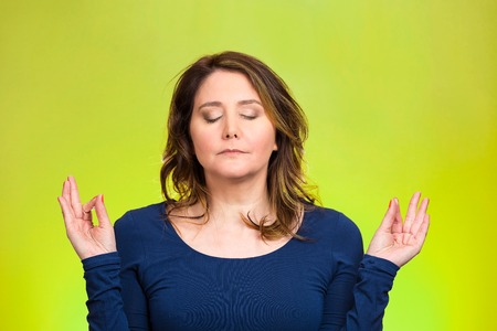 Closeup portrait peaceful young woman relaxing, meditating, in zen mode, isolated green background. Positive human emotions, facial expressions, attitude, life perception, situation, symbols, approach photo
